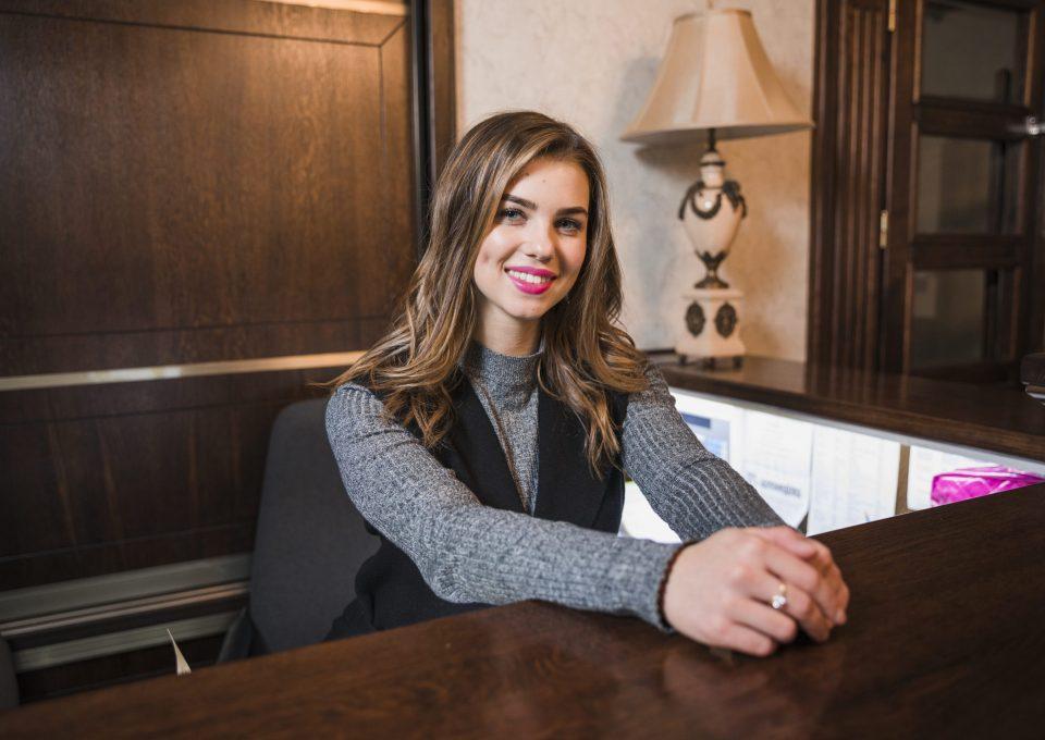 an-attractive-woman-at-reception-desk-looking-at-camera