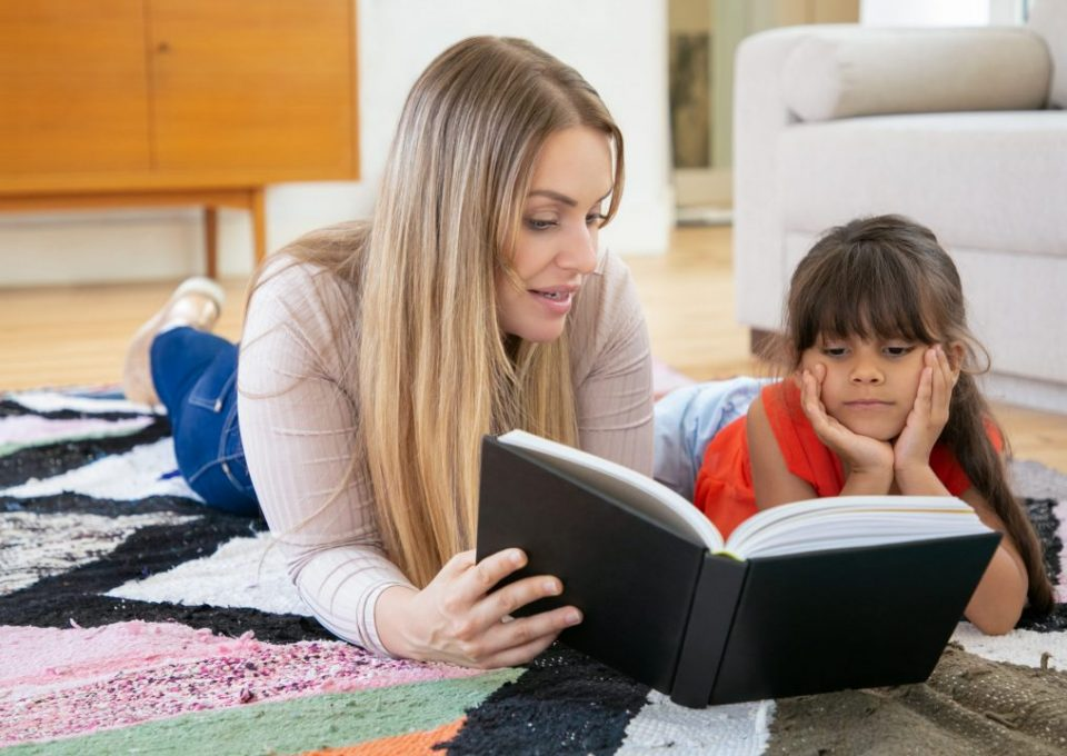Blonde mother lying on rug with daughter and reading book to her. Focused cute little girl learning to read with pretty mom, watching on text and listening carefully. Family time and education concept