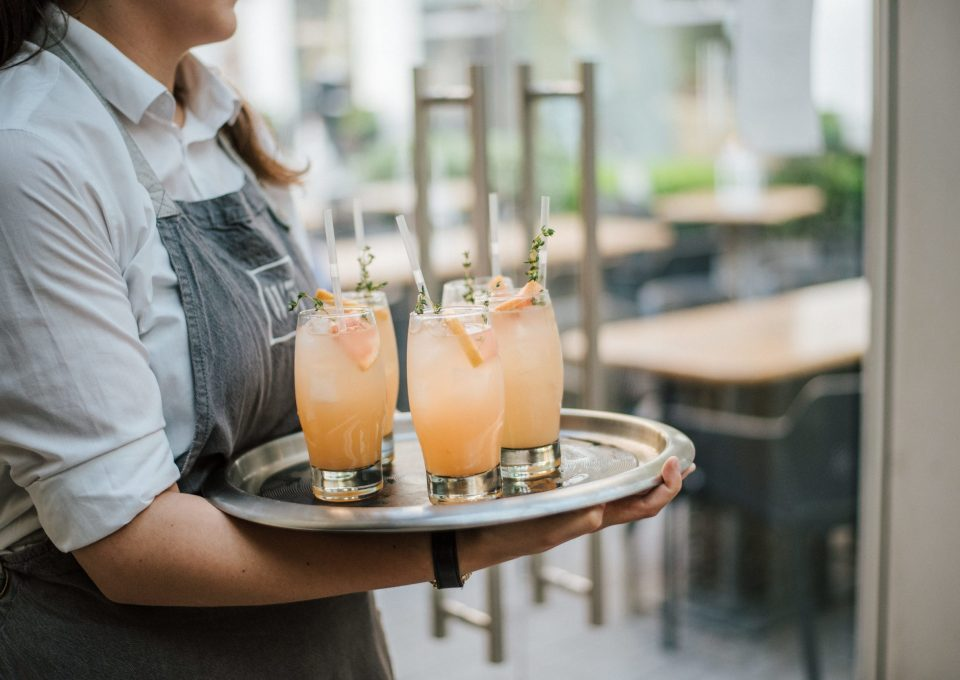 A closeup shot of a waiter serving cocktail with fresh oranges on a silver tray